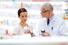 Αποθηκάριος και γυναίκα με το φάρμακο στο φαρμακείο στοκ εικόνες