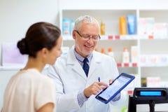 Αποθηκάριος και πελάτης με το PC ταμπλετών στο φαρμακείο στοκ εικόνα