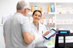 Αποθηκάριος και πελάτης με το PC ταμπλετών στο φαρμακείο στοκ φωτογραφία