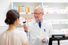 Αποθηκάριος με τη θεραπεία και πελάτης στο φαρμακείο στοκ φωτογραφία με δικαίωμα ελεύθερης χρήσης
