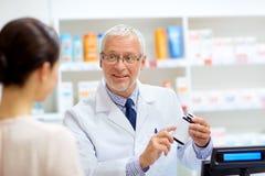 Αποθηκάριος με τη θεραπεία και πελάτης στο φαρμακείο στοκ φωτογραφία