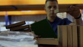 Αποθηκάριος που ελέγχει τις συσκευασίες στα ράφια στην αποθήκη εμπορευμάτων και που γράφει την έκθεση φιλμ μικρού μήκους