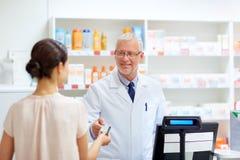 Αποθηκάριος που παίρνει την πιστωτική κάρτα πελατών στο φαρμακείο στοκ φωτογραφία με δικαίωμα ελεύθερης χρήσης