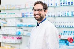 Αποθηκάριος στο φαρμακείο που στέκεται στο ράφι με τα φάρμακα στοκ φωτογραφία με δικαίωμα ελεύθερης χρήσης