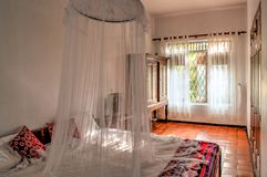 Αποικιακή κρεβατοκάμαρα ύφους με το κουνούπι καθαρό στοκ εικόνες