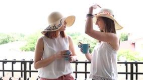 Αποκάλυψη της πυροβοληθείσας δύο όμορφης και πανέμορφης γυναίκας με τα μεγάλα καπέλα στον καφέ κατανάλωσης μπαλκονιών απόθεμα βίντεο