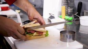Αποκάλυψη του στενού επάνω πυροβολισμού των χεριών μαγείρων που κόβουν ένα σάντουιτς απόθεμα βίντεο