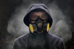 Αποκάλυψη ή armageddon έννοια Το άτομο φορά τη μάσκα αερίου Πολύς καπνός γύρω Στοκ Εικόνα