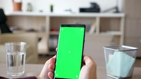 Αποκαλύπτοντας τον πυροβολισμό των χεριών ατόμων που κρατούν ένα smartpone με την πράσινη χλεύη χρώματος οθόνης επάνω φιλμ μικρού μήκους