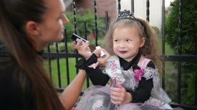 αποκριές ευτυχείς Η ελκυστική νέα γυναίκα με την λίγη χαριτωμένη κόρη προετοιμάζεται σε αποκριές υπαίθρια Mom με φιλμ μικρού μήκους