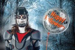 αποκριές ευτυχείς παίκτης χόκεϋ σε ένα κράνος και μια μάσκα χόκεϋ με ένα μπαλόνι ενάντια στο σκηνικό ή υπόβαθρο τρομακτικού δασικ Στοκ φωτογραφία με δικαίωμα ελεύθερης χρήσης