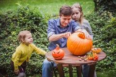 αποκριές ευτυχείς Χαράζοντας κολοκύθα πατέρων και δύο κορών για αποκριές έξω οικογένεια ευτυχής στοκ φωτογραφίες με δικαίωμα ελεύθερης χρήσης