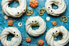 Αποκριές μεταχειρίζονται, λίγο επιδόρπιο τεράτων με doughnut που βυθίζεται στο wh Στοκ Φωτογραφίες