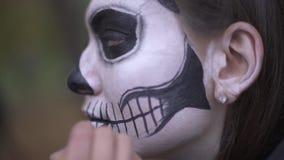 αποκριές Ο καλλιτέχνης Makeup εφαρμόζει τη σύνθεση στο πρόσωπο κοριτσιών απόθεμα βίντεο