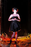 Αποκριές που φαίνονται μάγισσα σε ένα σκοτάδι με το μήλο Στοκ Φωτογραφία