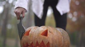 αποκριές Το κορίτσι ξοδεύει ένα μαχαίρι σε μια κολοκύθα αποκριών φιλμ μικρού μήκους
