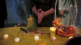 αποκριές Το κορίτσι σε ένα μαύρο φόρεμα ωθεί ένα μαχαίρι σε μια κολοκύθα απόθεμα βίντεο