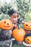 αποκριές Το παιδί έντυσε στο Μαύρο κοντά στο Λαμπραντόρ μεταξύ της διακόσμησης Jack-ο-φαναριών, τέχνασμα ή μεταχειρίζεται Μικρό κ Στοκ Φωτογραφία