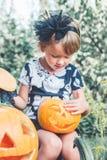 αποκριές Το παιδί που ντύνονται στο Μαύρο με το Jack-ο-φανάρι διαθέσιμο, το τέχνασμα ή μεταχειρίζονται Μικρό κορίτσι που κοιτάζει Στοκ εικόνες με δικαίωμα ελεύθερης χρήσης