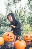 αποκριές Το παιδί που ντύνονται στο Μαύρο με το Jack-ο-φανάρι διαθέσιμο, το τέχνασμα ή μεταχειρίζονται Εκφοβισμός της κολοκύθας μ Στοκ εικόνες με δικαίωμα ελεύθερης χρήσης