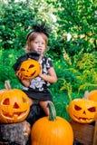 αποκριές Το παιδί που ντύνονται στο Μαύρο με το Jack-ο-φανάρι διαθέσιμο, το τέχνασμα ή μεταχειρίζονται Κολοκύθα λαβής μικρών κορι Στοκ Εικόνες