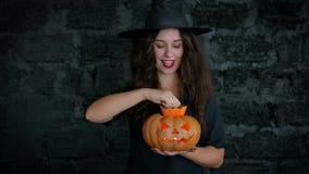 αποκριές Το χαριτωμένο κορίτσι παρουσιάζει εύθυμη μάγισσα Είναι ντυμένη σε ένα μαύρα φόρεμα και ένα καπέλο Κολοκύθα εκμετάλλευσης απόθεμα βίντεο