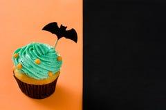 Αποκριές cupcake με ένα ρόπαλο στο μαύρο και πορτοκαλί υπόβαθρο Στοκ Εικόνες