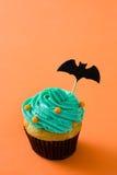 Αποκριές cupcake με ένα ρόπαλο στο πορτοκαλί υπόβαθρο Στοκ Εικόνες