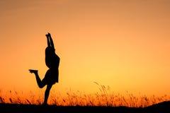 απολαύστε χαλαρώνει τη γυναίκα ηλιοβασιλέματος σκιαγραφιών Στοκ Φωτογραφία
