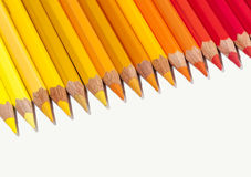 Απομονωμένα κόκκινα κίτρινα και πορτοκαλιά μολύβια στη γραμμή Στοκ Εικόνες