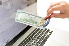 Απομονωμένα χρήματα του ατόμου που τραβούν τα χρήματα από το lap-top με το μαγνήτη Στοκ φωτογραφία με δικαίωμα ελεύθερης χρήσης