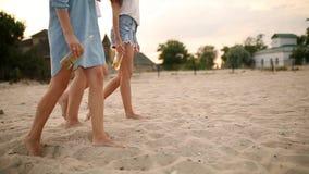 Απομονωμένη άποψη τριών ζευγαριών των λεπτών θηλυκών ποδιών με τα μπουκάλια γυαλιού του ποτού στα χέρια που περπατούν στην παραλί απόθεμα βίντεο