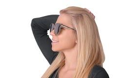 Απομονωμένη νέα κυρία στα γυαλιά ηλίου που χαμογελά στο άσπρο υπόβαθρο Στοκ Εικόνες