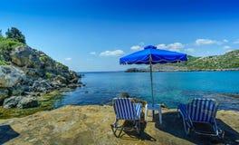 Απομονωμένη παραλία κόλπων του Anthony Quinn με την ομπρέλα και τις καρέκλες στοκ εικόνες
