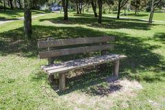 Απομονωμένος ξύλινος πάγκος σε ένα πάρκο που περιβάλλεται από τη χλόη και τα δέντρα υπόλοιπο lap-top εστίασης φλυτζανιών έννοιας Στοκ Φωτογραφίες