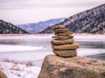 Απομονωμένος τύμβος βράχου με το παγωμένο υπόβαθρο λιμνών Στοκ Φωτογραφία
