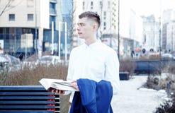 απομονωμένο επιχείρηση άτομο ανασκόπησης πέρα από το λευκό Ένα άτομο με ένα βιβλίο και ένα lap-top Ο τύπος μιλά μέσω του τηλεφώνο Στοκ Εικόνες