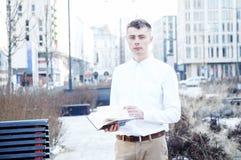 απομονωμένο επιχείρηση άτομο ανασκόπησης πέρα από το λευκό Ένα άτομο με ένα βιβλίο και ένα lap-top Ο τύπος μιλά μέσω του τηλεφώνο Στοκ Φωτογραφία