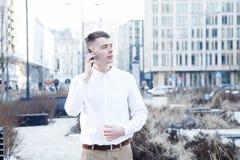 απομονωμένο επιχείρηση άτομο ανασκόπησης πέρα από το λευκό Ένα άτομο με ένα βιβλίο και ένα lap-top Ο τύπος μιλά μέσω του τηλεφώνο Στοκ Φωτογραφίες
