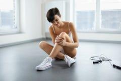 απομονωμένο λευκό ποδιών ανασκόπησης ζημία Όμορφη γυναίκα που αισθάνεται τον πόνο στο γόνατο, επίπονο γόνατο Στοκ Φωτογραφία