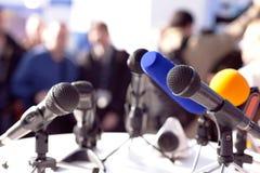 απομονωμένο λευκό Τύπου μικροφώνων ανασκόπησης διάσκεψη