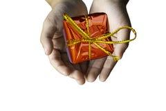 Απομονωμένο κόκκινο κιβωτίων δώρων εκμετάλλευσης χεριών για τους εορτασμούς σε ένα μόριο στοκ φωτογραφία με δικαίωμα ελεύθερης χρήσης