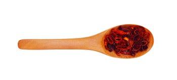 Απομονωμένο ξύλινο κουτάλι με το πιπέρι τσίλι που κόβεται στα δαχτυλίδια Στοκ Εικόνα