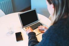 απομονωμένο οπισθοσκόπο λευκό Η νέα επιχειρηματίας κάθεται στο στρογγυλό άσπρο πίνακα και χρησιμοποιεί το lap-top Κορίτσι που εργ Στοκ Φωτογραφία