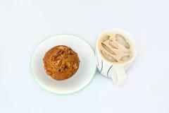 Απομονωμένο muffin καρυδιών σε ένα πιάτο με τον παγωμένο καφέ Στοκ Εικόνες