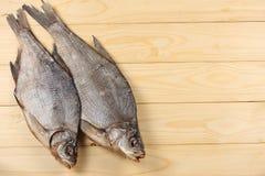 Αποξηραμένα ψάρια στον πίνακα Αλμυρά ξηρά ψάρια ποταμών σε ένα ελαφρύ ξύλινο υπόβαθρο Τοπ άποψη με το διάστημα αντιγράφων Στοκ Φωτογραφία