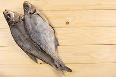 Αποξηραμένα ψάρια στον πίνακα Αλμυρά ξηρά ψάρια ποταμών σε ένα ελαφρύ ξύλινο υπόβαθρο Τοπ άποψη με το διάστημα αντιγράφων Στοκ Εικόνα
