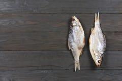 Αποξηραμένα ψάρια στον πίνακα Αλμυρά ξηρά ψάρια ποταμών σε ένα σκοτεινό ξύλινο υπόβαθρο Τοπ άποψη με το διάστημα αντιγράφων Στοκ εικόνες με δικαίωμα ελεύθερης χρήσης