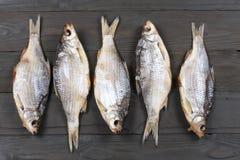 Αποξηραμένα ψάρια στον πίνακα Αλμυρά ξηρά ψάρια ποταμών σε ένα σκοτεινό ξύλινο υπόβαθρο Τοπ άποψη με το διάστημα αντιγράφων Στοκ φωτογραφία με δικαίωμα ελεύθερης χρήσης