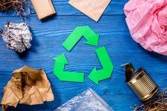Απορρίματα για την ανακύκλωση με την ανακύκλωση του συμβόλου στην μπλε ξύλινη τοπ άποψη υποβάθρου Στοκ εικόνα με δικαίωμα ελεύθερης χρήσης